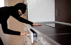 Thief in black clothes robbed home Stock Photo