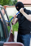 Thief breaking into the car Stock Image