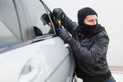Thief breaking into a car Royalty Free Stock Photos