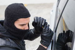 Thief breaking into a car Stock Images