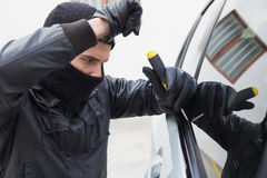 Thief breaking into a car Royalty Free Stock Images