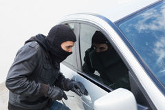 Thief breaking into a car. In broad daylight Stock Photography