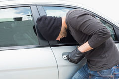 Thief breaking into a car Stock Photo