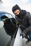 Thief breaking into a car Royalty Free Stock Photography