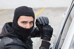 Thief breaking into a car Royalty Free Stock Photo