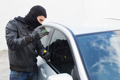 Thief breaking into a car Royalty Free Stock Image