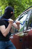 A thief breaking into a car Stock Photography