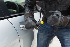 Thief breaking into car with screwdriver Royalty Free Stock Photo