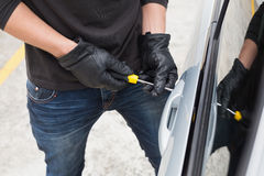 Thief breaking into car with screwdriver stock photo