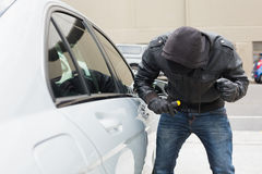 Thief breaking into car with screwdriver. In broad daylight Stock Photos