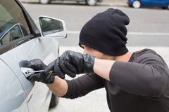 Thief breaking into car with screwdriver. In broad daylight Royalty Free Stock Images