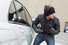 Thief breaking into car with screwdriver. In broad daylight Royalty Free Stock Photos