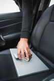 Thief breaking into car and stealing. In broad daylight Royalty Free Stock Image