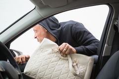 Thief breaking into car and stealing hand bag. In broad daylight Stock Images