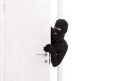 Thief breaking into a room and carefully looking around. Studio shot of a stealthy thief breaking into a room through a door and carefully looking around  on Royalty Free Stock Images