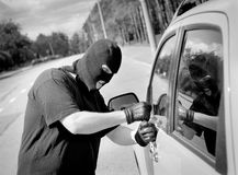 Thief breaks into a car door. On the street stock image