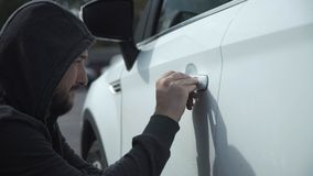 The thief breaks the car. The thief wearing hoodie breaks the car door with a metal tool takes bag and gone Royalty Free Stock Image