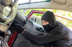 Thief breaks the door in the car. Thief in the mask breaks the door in the car Stock Photography