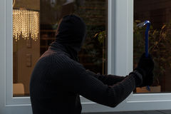 Thief breaks the glass. With a crowbar Stock Photo