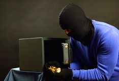 The thief breaks the safe with a combination lock. The attacker opens the safe on a black background royalty free stock images