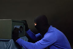 The thief breaks the safe with a combination lock. The attacker opens the safe on a black background stock photos