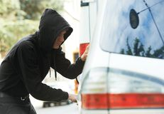 Thief burglar at automobile car stealing. Thief stealing automobile car at daylight street in city stock image