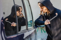 Thief burglar breaking smashing the car window. Transportation, crime and ownership concept - Male hooded thief burglar breaking smashing the car window royalty free stock images