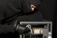 Thief burglar and home safe. Thief burglar stealing money during home safe codebreaking Stock Photography