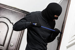 Thief burglar at house breaking. Thief Burglar opening metal door with a crowbar during house breaking Royalty Free Stock Photos