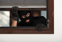 Thief burglar at house breaking. Thief Burglar opening window during house breaking Royalty Free Stock Photo