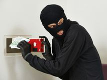 Thief burglar at house safe breaking. Thief burglar stealing euro money during home safe codebreaking royalty free stock photography