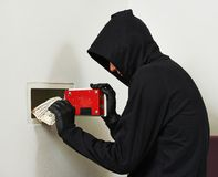 Thief burglar at house safe breaking. Thief burglar stealing euro money during home safe codebreaking Stock Images
