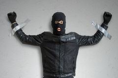 Thief or burglar masked with balaclava is caught and is taped to the wall with duct tape. Royalty Free Stock Photo