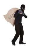 Thief carrying a large bag of money. Thief in black clothes wearing a balaclava carrying a large bag of money with a dollar sign over his shoulder isolated on Royalty Free Stock Photography