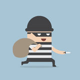 Thief cartoon holding knife in his hand and carrying a money bag Royalty Free Stock Photography