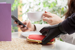 Thief in a coffee shop. Thief stealing a wallet in coffee shop Stock Photos