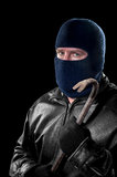 Thief with crowbar. A thief wearing a ski mask to hide his identity holds a crowbar and prepares to commit a crime Stock Image