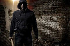 Thief in a dark alley. Thief in the hood on a dark alley stock image