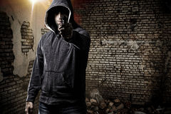 Thief in a dark alley. Thief in the hood on a dark alley stock photography