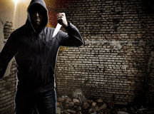 Thief in a dark alley. Thief in the hood on a dark alley royalty free stock image