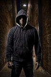 Thief on a dark alley. Thief in the hood on a dark alley royalty free stock photo