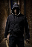 Thief on a dark alley. Thief in the hood on a dark alley royalty free stock photography