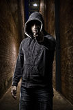 Thief on a dark alley. Thief in the hood pointing a gun, on a dark alley royalty free stock photography