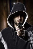 Thief on a dark alley. Thief pointing a gun on a dark alley Royalty Free Stock Image