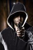 Thief on a dark alley. Thief pointing a gun on a dark alley royalty free stock image