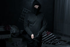 Thief in a dark room. Masked thief in a messy dark room Stock Photography