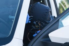 The thief disables the electronic alarm system of the car in the cabin before theft close-up. The thief disables the electronic alarm  system of the car in the stock photo