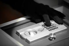 Thief entering password on safe, Stock Photo