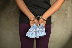 Thief. Female thief cuffed hands with US Dollars in her hands stock images