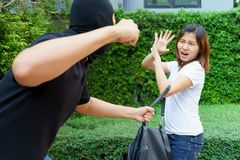 Thief fighting and stealing handbag from screaming asian woman a. Thief fighting and stealing handbag from screaming asian women at park Royalty Free Stock Images